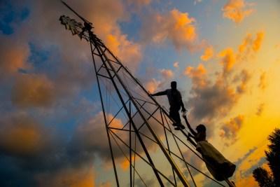 Alum Creek Farm Wedding bride and groom climb windmill at sunset