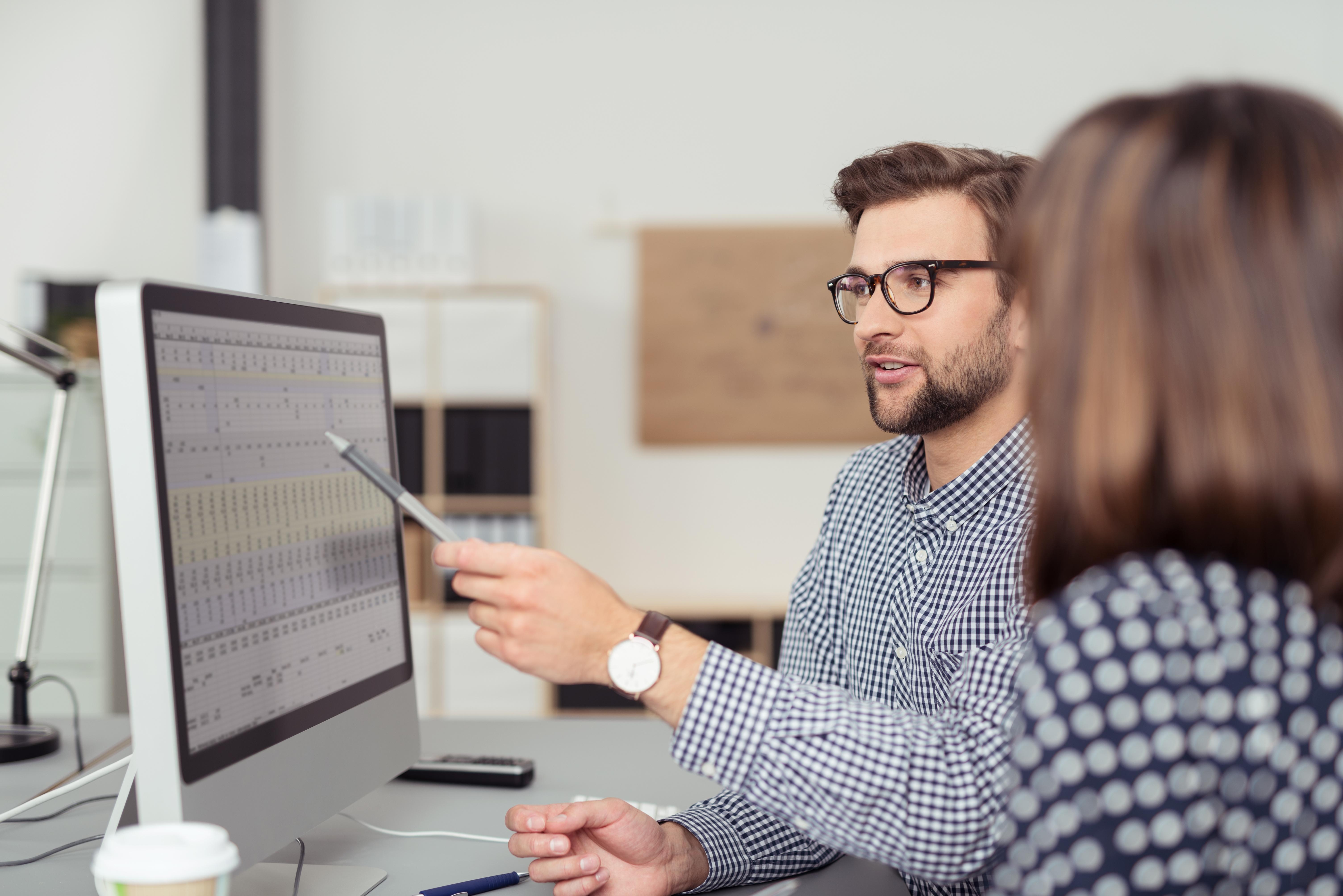 man-training-woman-on-computer