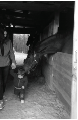 Jessica Griffith and her son walk through the barn and is greeted by Lena. Griffith trained the horse from a young age. Photo courtesy by L.Cowan/Setonian