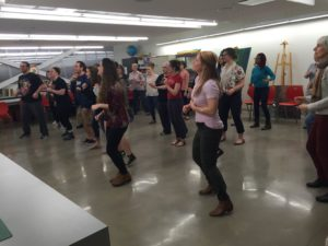 Participation engage in an experiential dance session. The dance is meant to make those who participate feel empowered. Photo courtesy of C. Arida