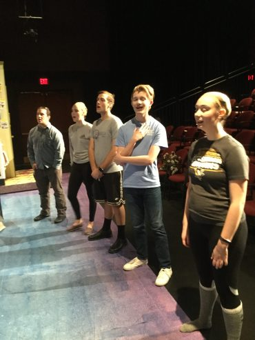 Cast members sing during warm-ups before the show.