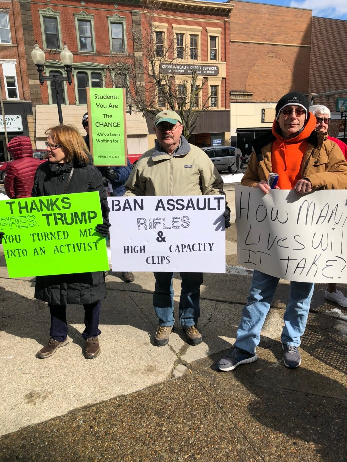 From left to right: Jane and Gary Armbrest from Vandergrift, Pa. and Brian Susco from Salix, Pa. hold their signs at Greensburg's March for Our Lives rally on March 23.