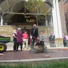 Steven Bassett, chair of the biology department, shovels dirt onto the tree dedicated to Suzanne Rogers on Oct. 12.