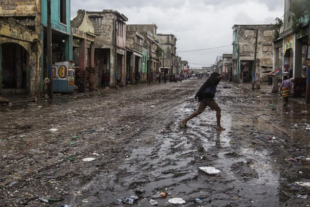 """In this photo released by UNICEF, a woman crosses the street on a flood effected road as hurricane Matthew passes over on October 4, 2016 Port au Prince. Weakened but still dangerous, Hurricane Matthew churned toward the Bahamas Wednesday en route to an already jittery Florida after killing at least nine people in the Caribbean in a maelstrom of wind, mud and water. / AFP PHOTO / UNICEF / Logan ABASSI / RESTRICTED TO EDITORIAL USE - MANDATORY CREDIT """"AFP PHOTO / UNICEF/ Logan ABASSI - NO MARKETING - NO ADVERTISING CAMPAIGNS - DISTRIBUTED AS A SERVICE TO CLIENTS"""