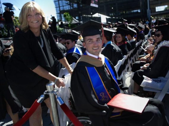 Entregan diploma a madre que tomó clases con hijo paralítico
