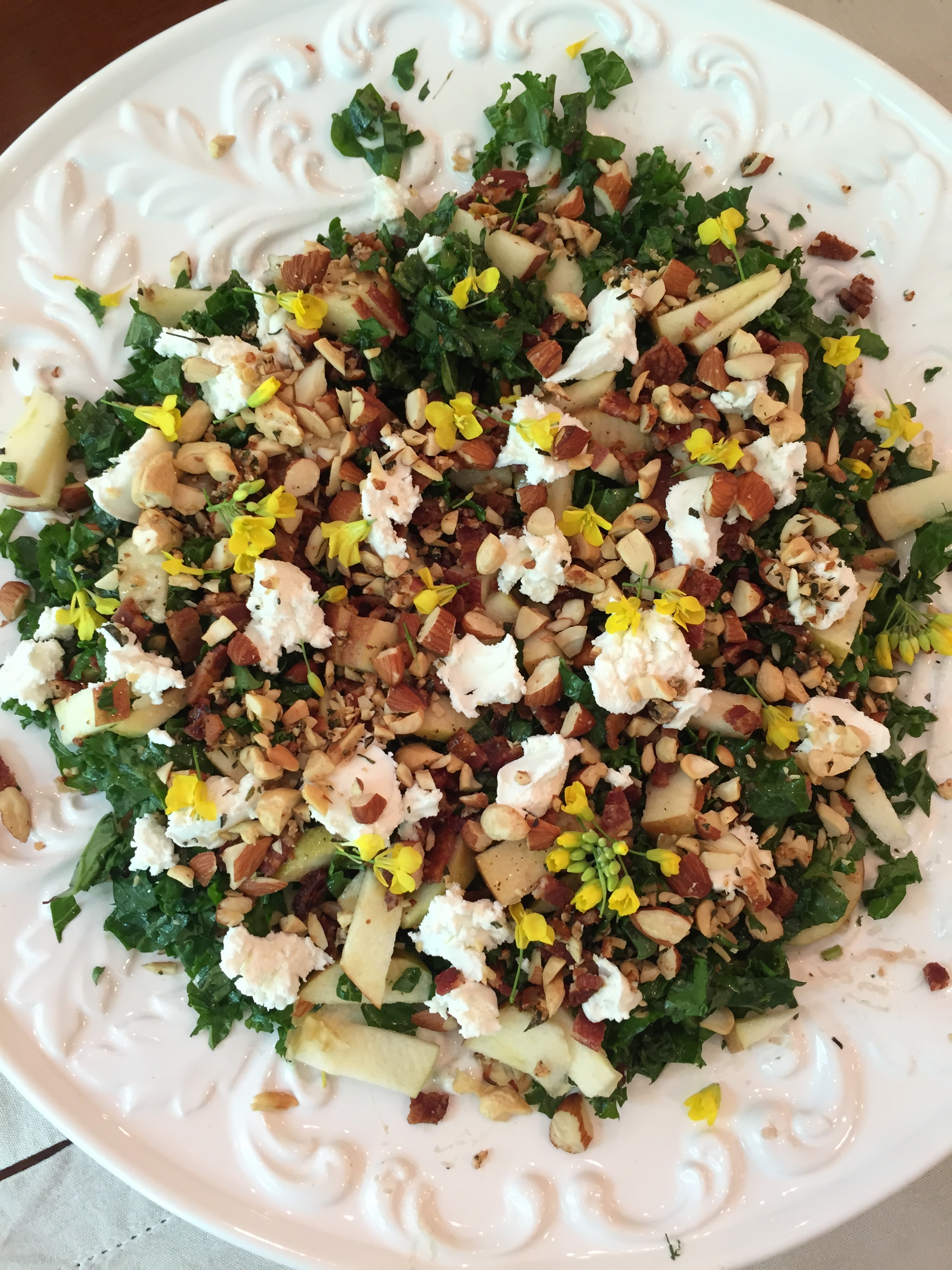 kale salad recipe with apples, bacon, rosemary nuts, goat cheese, edible flowers; CSA meal
