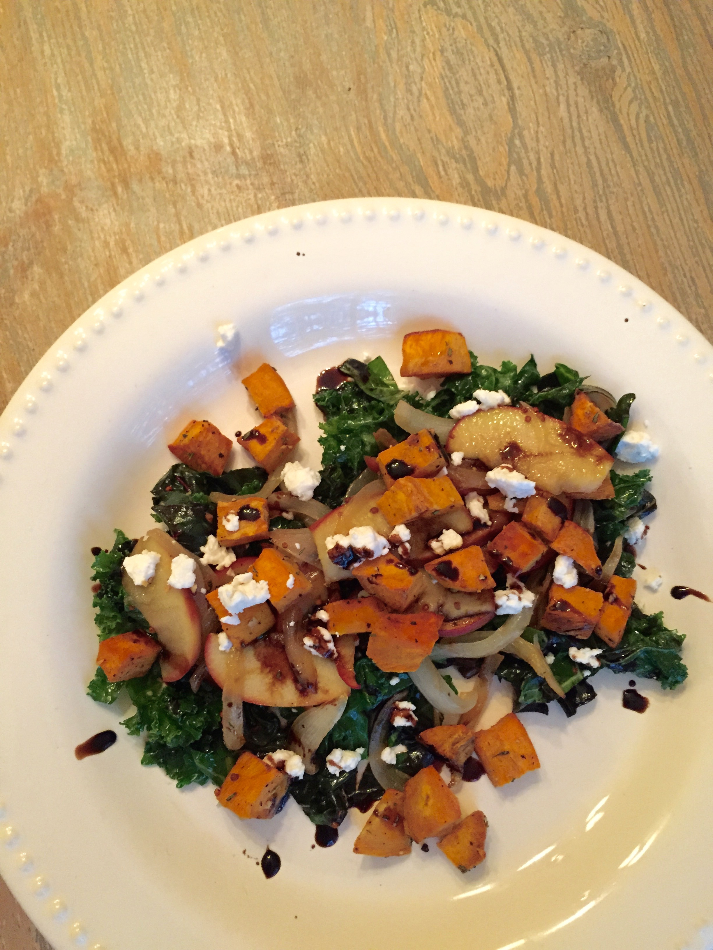 warm roasted sweet potato kale salad with caramelized onions and apples, balsamic glaze, pecans, goat cheese
