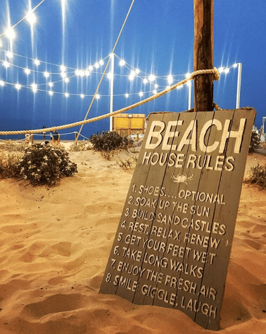 Evening scene at a beach resort with a sign displaying comical beach rules