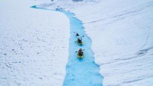 Three kayakers paddle down glacier lake meltwater