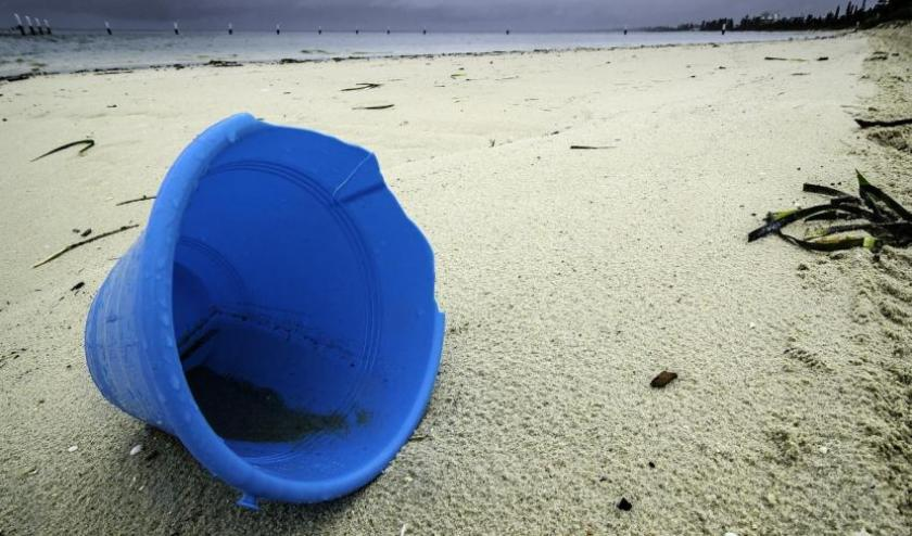 blue sand bucket on the beach