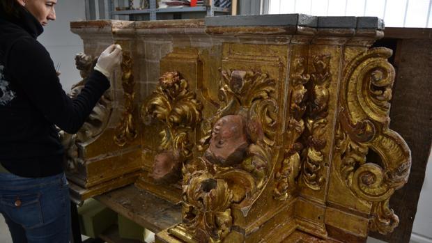 Una restauradora trabajando en una de las piezas del retablo del Rosario