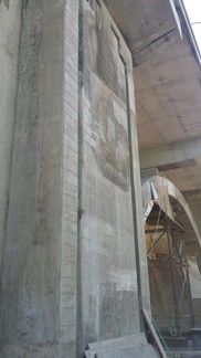 Sprayed concrete - shotcrete - used to repair pier below bridge deck.