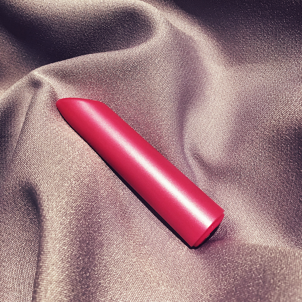Photo of pink tube-shaped bullet vibrator on purple cloth