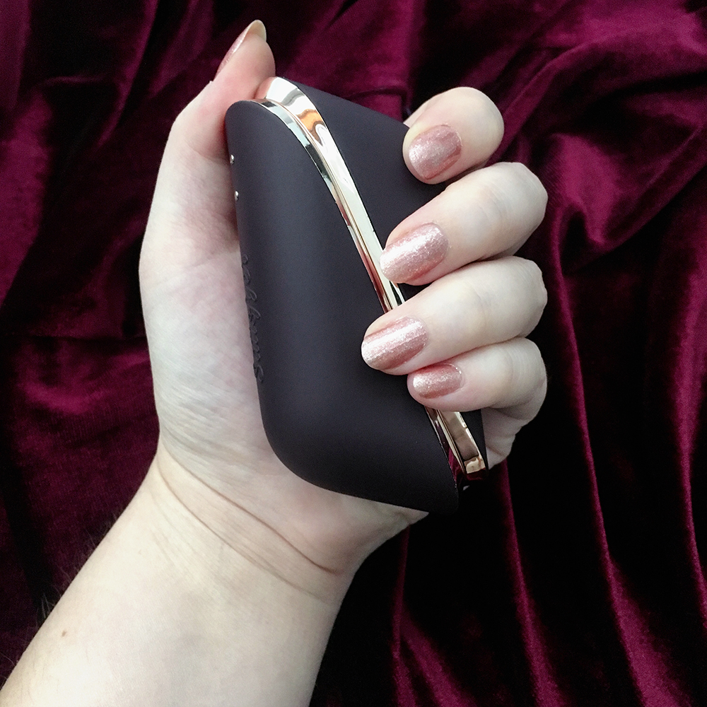above photo of dark purple Satisfyer Pro Traveler on red velvet background, held in white woman's hand