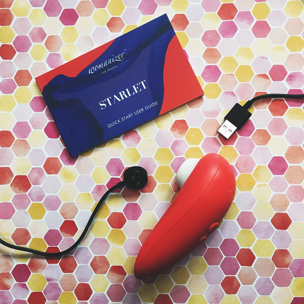 Photo of peach oval shaped Starlet 2 on its side, next to instruction book and charging cable