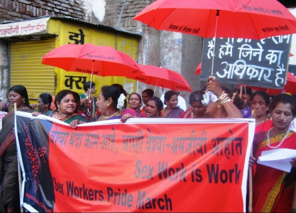 "Women at sex workers pride march holding red umbrellas and a banner which says ""Sex work is work"""