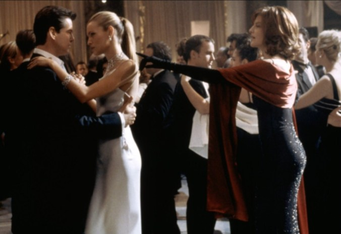Brosnan dances with another woman with Russo tapping on her shoulder to cut in