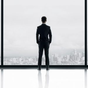 An image from Fifty Shades of Grey of Christian Grey, standing in a window looking out over Seattle