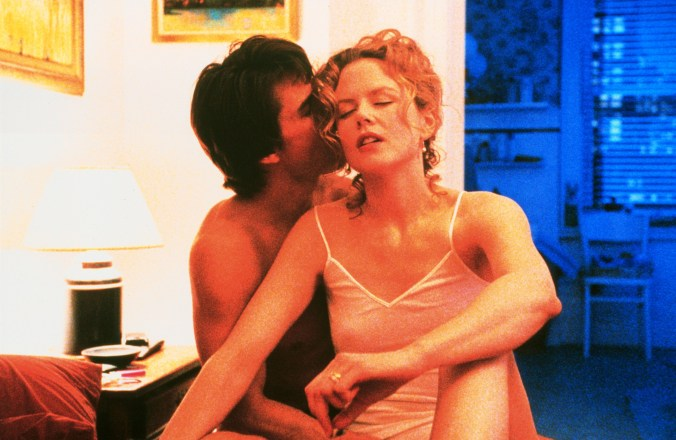 Cruise and Kidman, in their underwear, sitting on a bed and he is kissing her cheek