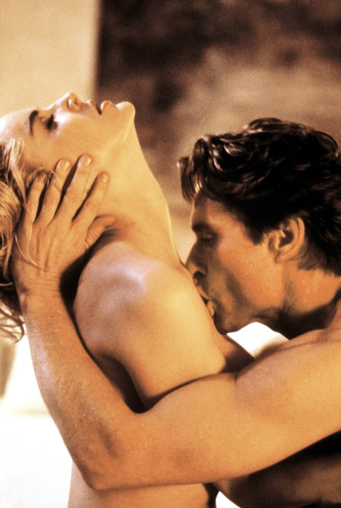 Stone leaning back as Douglas kisses the front of her neck. Both are naked.