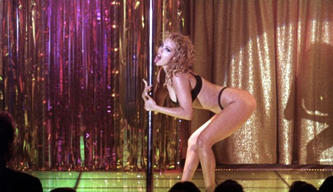An image from Showgirls showing Nomi licking a pole