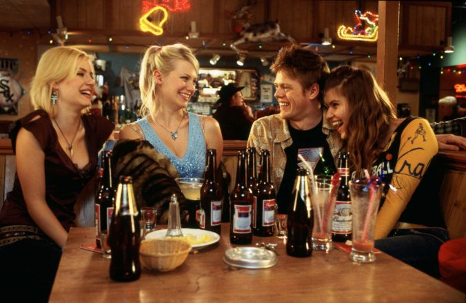 An image from Love Actually showing Colin and the three American women