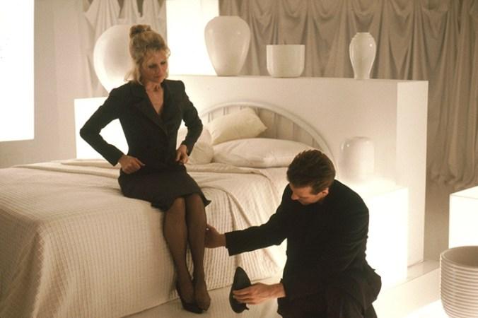 Elizabeth sat in a bed while John feels her calf