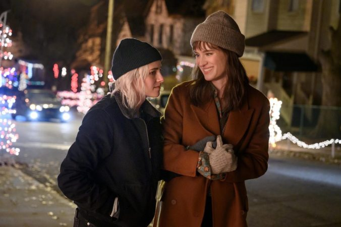 A scene from Happiest Season of Harper and Abby walking through a snowy town