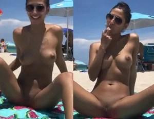 Mulher pelada se masturbando em uma praia de nudismo