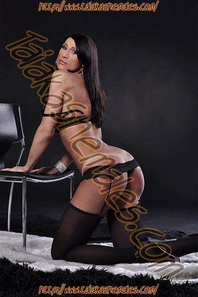 Bella travesti desnuda en lencería negra Luna Kiss de rodillas.