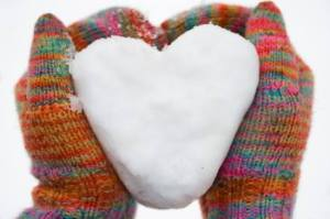 Image: Hands in multicolor gloves holding a snow heart