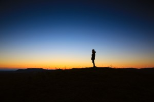 Image: A person standing alone on a ridge at sunset