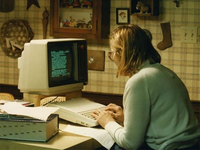 Mulher usando computador antigo