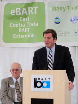 BART Director Thomas Blalock, seated, and Representative John Garamendi at the lectern.