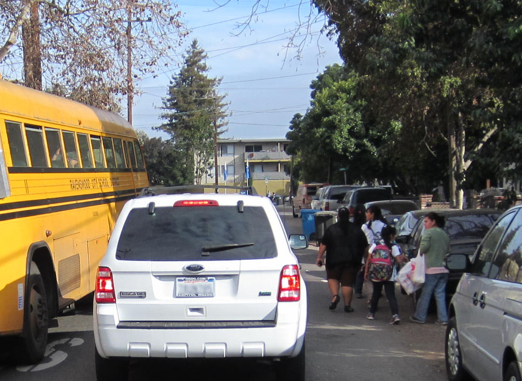 Children walking home from school share the road with vehicles on Scofield Avenue in East Palo Alto, where the city plans to install sidewalks where none exist today. Photo: Andrew Boone