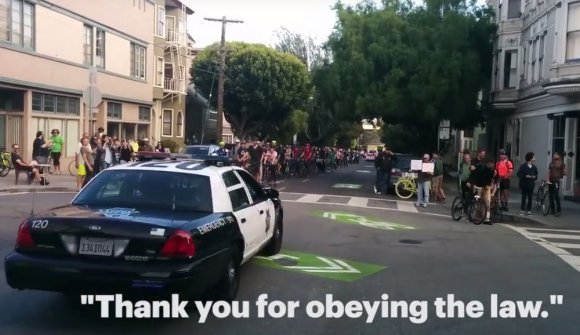 An SFPD driver thanks bike commuters for obeying the letter of the stop sign law at last week's demonstration. Screenshot from The Wigg Party via Uptown Almanac