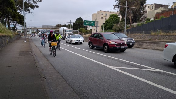 Wide, buffered bike lanes help make cycling safer and more comfortable, although it's unclear why the protection bollards don't continue the whole way. Photo: Streetsblog.