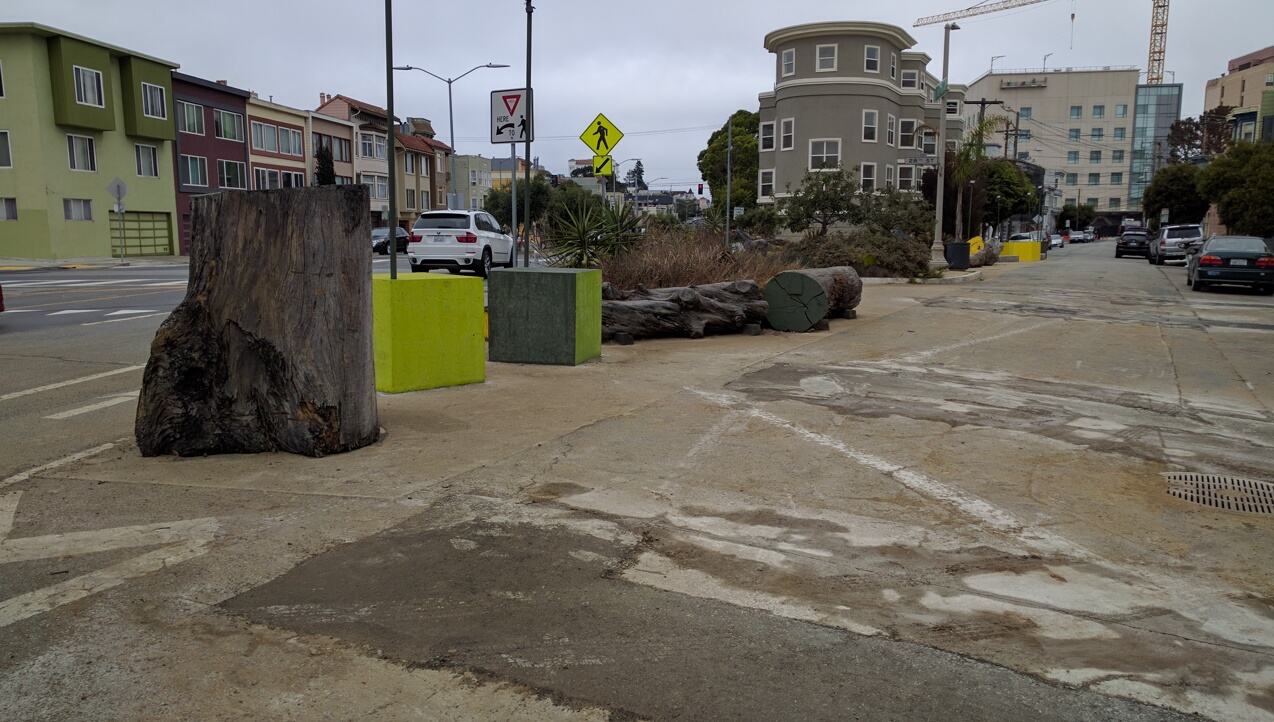 Although construction is not yet complete, the small park is really taking shape. Note the use of logs and concrete art to make sure cars can't intrude on this public space. Although it is permeable to pedestrians and slow moving bikes. Photo: Streetsblog.