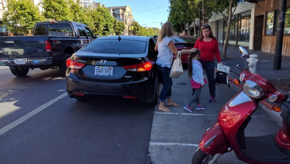 A car discharging passengers on Valencia. Will a new education campaign get ride-hails out of the bike lane? Photo: Streetsblog