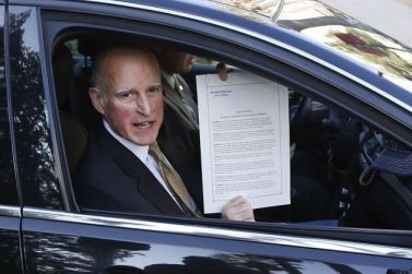 Gov. Jerry Brown displays proclamation declaring end to prison overcrowding by Rich Pedroncelli, AP