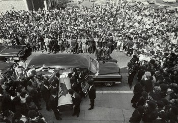 The body of George Jackson, assassinated at San Quentin Prison on Aug. 21, 1971, is brought into St. Augustine Episcopal Church for his funeral on Aug. 28. By the time the funeral ended and the pallbearers carried the coffin back out, 8,000 people were waiting outside. – Photo: Stephen Shames