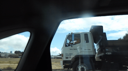 """CBI's dump truck leaves the main entrance of Site 31 on its way to enter the same site by its back gate in this photo taken from the car that """"chased"""" the truck. – Photo: Carol Harvey"""