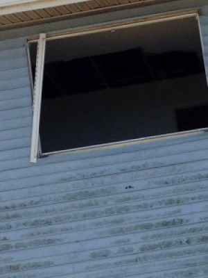 This broken out window is in a house close to Sandy Agee's that has been radiologically impacted. When that condemned house is demolished, will Sandy and her children be showered with radioactive fallout? – Photo: Carol Harvey