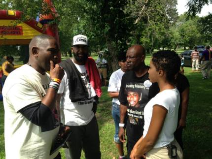 Ron Davis, father of Jordan Davis, the young man murdered over loud music, Tracy Martin, Trayvon's father, and Uncle Bobby consult in a Ferguson park. They have been supporting other families facing similar tragedies. – Photo: Kumasi Aaron