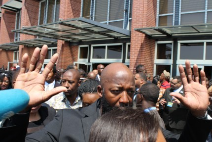 Tracy Martin, Trayvon Martin's father, holds his hands up as he leaves the church after Michael Brown's funeral. Contrary to the myth of the Black boy going astray for want of a male role model, many of the murdered young men, such as Jordan, Trayvon, Oscar and Michael, had strong father figures, were unarmed and doing nothing to justify their murder. – Photo: JR Valrey, Block Report