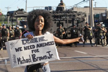 A woman demanding answers turns away from a line of militarized police and toward the crowd of protesters. – Photo: J.B. Forbes, St. Louis Post-Dispatch/AP