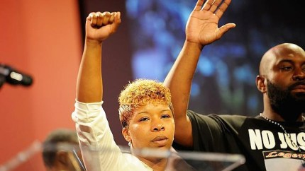 Leslie McSpadden and Michael Brown Sr., Mike's parents, signal victory and surrender – victory over police terrorism through the surrender of their son. Leslie says Mike deliberately distracted the killer cop so his friend, Dorian Johnson, could escape.
