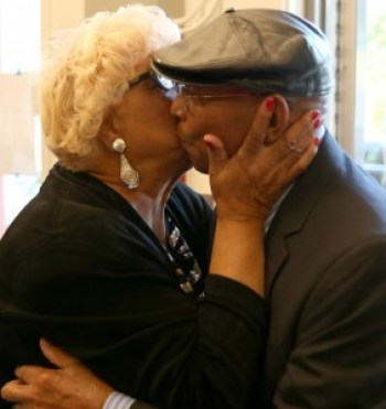 Rochelle Metcalfe delivers a big birthday kiss, to Dr. Willie Ratcliff's delight. – Photo: Malaika Kambon