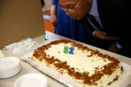 Dr. Ratcliff blows out the candles on his 82nd birthday cake, a deliciously fruity carrot cake baked by Auntie April, whose popular restaurant is at 4618 Third St. in Bayview Hunters Point and whose family comes from the same historic Black town of East Liberty in Deep East Texas where Dr. Ratcliff was born and raised. – Photo: Malaika Kambon