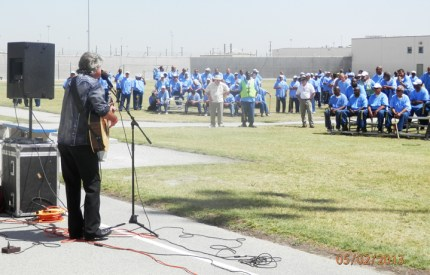 "CSATF prisoners listen to a visiting missionary in the ""hot flaming sun"" of the San Joaquin Valley. For prisoners whose color has faded from decades in isolation, with rare exposure to sunlight, the hot sun of the San Joaquin Valley is good medicine."